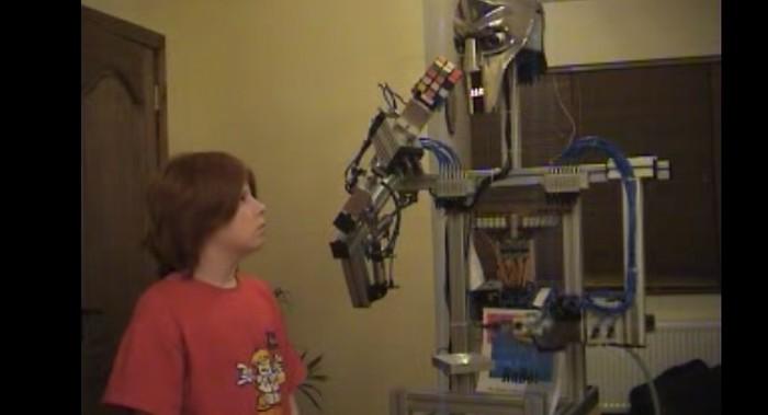 robo segurando um cubo e menino olhando