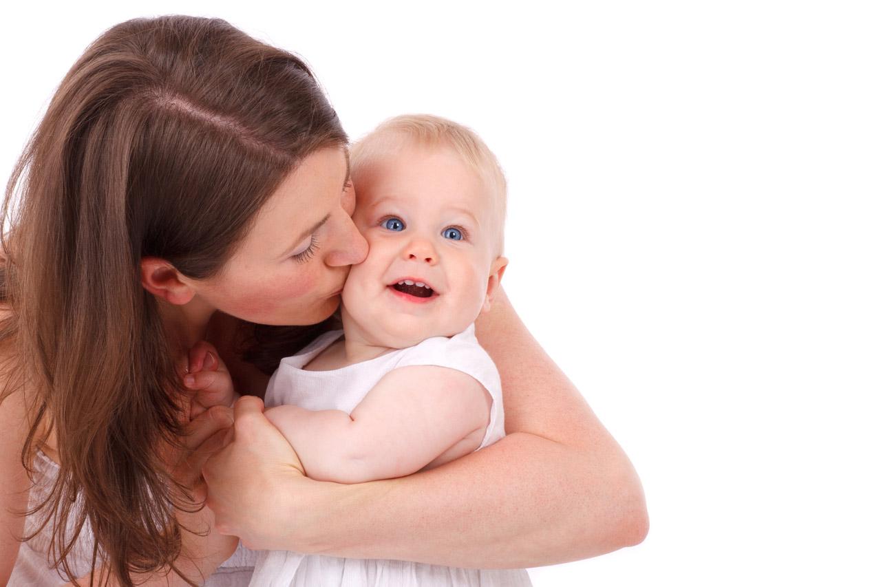 mãe beijando um bebê no rosto